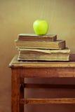 Σωρός των παλαιών βίβλων και του πράσινου μήλου στην παλαιά καρέκλα Στοκ εικόνα με δικαίωμα ελεύθερης χρήσης
