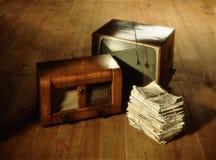 Σωρός των παλαιών εφημερίδων, του ραδιοφώνου και της τηλεόρασης στο ξύλινο πάτωμα Στοκ Εικόνα
