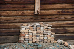 Σωρός των παλαιών τούβλων στον τοίχο υποβάθρου ένα ξύλινο σπίτι στοκ εικόνα με δικαίωμα ελεύθερης χρήσης
