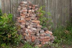 Σωρός των παλαιών τούβλων στο υπόβαθρο φρακτών Στοκ Φωτογραφίες