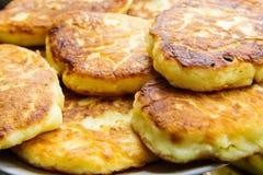 Σωρός των πρόσφατα τηγανισμένων σπιτικών χνουδωτών τηγανιτών από το τυρί εξοχικών σπιτιών στο πιάτο Ορεκτικός χρυσός στενός επάνω στοκ φωτογραφίες