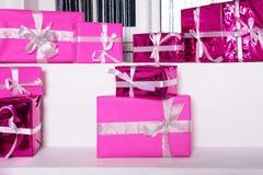 Σωρός των ρόδινων κιβωτίων δώρων εορτασμού με τα τόξα κορδελλών στον άσπρο πίνακα Έννοια χειμερινών διακοπών Στοκ εικόνα με δικαίωμα ελεύθερης χρήσης