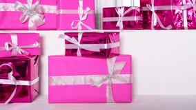 Σωρός των ρόδινων κιβωτίων δώρων εορτασμού με τα τόξα κορδελλών στον άσπρο πίνακα Έννοια χειμερινών διακοπών Στοκ Εικόνες