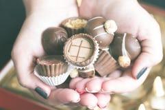 Σωρός των σοκολατών στα χέρια των γυναικών Στοκ εικόνα με δικαίωμα ελεύθερης χρήσης