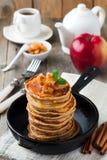 Σωρός των τηγανιτών από το αλεύρι φαγόπυρου με τα ψημένα μήλα και την κανέλα στο παλαιό ξύλινο υπόβαθρο πρόγευμα υγιές Στοκ Εικόνα