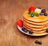 Σωρός των τηγανιτών με το φρέσκες βακκίνιο και τη φράουλα στο ξύλο Στοκ Φωτογραφίες
