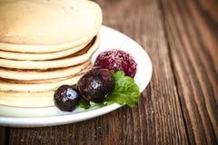 Σωρός των τηγανιτών στο άσπρο πιάτο με τα παγωμένες μούρα και τη μέντα Στοκ φωτογραφία με δικαίωμα ελεύθερης χρήσης