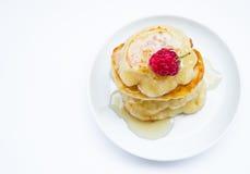 Σωρός των τηγανιτών στο πιάτο, τα σμέουρα και το μέλι, τοπ άποψη Στοκ Εικόνα