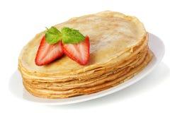 Σωρός των τηγανιτών. crepes με το βούτυρο και τη φράουλα που απομονώνονται επάνω Στοκ Εικόνες