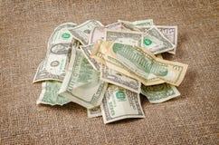 Σωρός των τραπεζογραμματίων αμερικανικών δολαρίων που τσαλακώνονται στο υπόβαθρο γιούτας Στοκ εικόνες με δικαίωμα ελεύθερης χρήσης