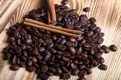 Σωρός των φασολιών καφέ με την κανέλα στον ξύλινο πίνακα για το backgroun Στοκ φωτογραφία με δικαίωμα ελεύθερης χρήσης