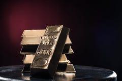 Σωρός των χρυσών πλινθωμάτων στον πίνακα ενάντια στοκ φωτογραφία