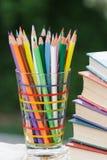 Σωρός των χρωματισμένων μολυβιών σε ένα γυαλί, βιβλία Στοκ φωτογραφία με δικαίωμα ελεύθερης χρήσης