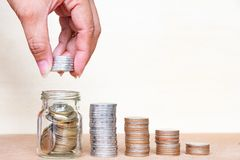σωρός χρημάτων χεριών έννοιας νομισμάτων που προστατεύει την αποταμίευση Νομίσματα σωρών λαβής δάχτυλων στο μπουκάλι arrang Στοκ Φωτογραφίες