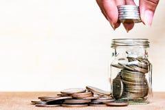 σωρός χρημάτων χεριών έννοιας νομισμάτων που προστατεύει την αποταμίευση Νομίσματα σωρών λαβής δάχτυλων στο μπουκάλι arrang Στοκ εικόνα με δικαίωμα ελεύθερης χρήσης