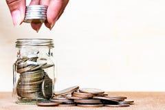 σωρός χρημάτων χεριών έννοιας νομισμάτων που προστατεύει την αποταμίευση Νομίσματα σωρών λαβής δάχτυλων στο μπουκάλι arrang Στοκ Εικόνα