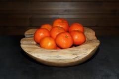 Σωρός tangerines σε ένα ξύλινο κύπελλο στο σκοτεινό πίνακα στοκ εικόνα