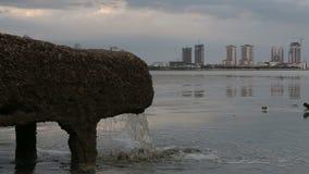 σωλήνας του νερού υπονόμων από το σύστημα αποχετεύσεων άμεσα κοντά στη θάλασσα στην πόλη με τους ουρανοξύστες απόθεμα βίντεο