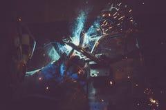 Σωλήνας χάλυβα συγκόλλησης ατόμων σε έναν πίνακα εργασίας σε ένα βιομηχανικό εργαστήριο, που παράγει τον μπλε και πράσινο καπνό,  Στοκ Φωτογραφία