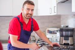 Σόμπα αερίου καθορισμού Handyman στην κουζίνα στοκ εικόνες