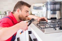 Σόμπα αερίου καθορισμού Handyman στην κουζίνα στοκ εικόνα