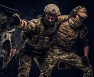 Σύγκρουση αγώνα, ειδική αποστολή Ο στρατιωτικός φέρνοντας συμπαίκτης στρατιωτών από το πεδίο μάχη Φωτογραφία στούντιο ενάντια στο στοκ φωτογραφίες