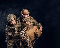 Σύγκρουση αγώνα, ειδική αποστολή, υποχώρηση Ο στρατιωτικός γιατρός διασώζει τον πληγωμένο συμπαίκτη του που φέρνει τον από το πεδ στοκ φωτογραφία
