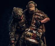 Σύγκρουση αγώνα, ειδική αποστολή, υποχώρηση Ο στρατιωτικός γιατρός διασώζει τον πληγωμένο συμπαίκτη του που φέρνει τον από το πεδ στοκ φωτογραφία με δικαίωμα ελεύθερης χρήσης