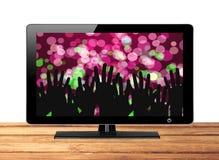 Σύγχρονα εορταστικά φω'τα οθόνης TV στον ξύλινο πίνακα Στοκ Φωτογραφία