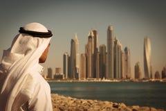 Σύγχρονα κτήρια στη μαρίνα του Ντουμπάι, Ε.Α.Ε. Το άτομο στο αραβικό φόρεμα κοιτάζει Στοκ Φωτογραφίες
