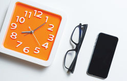 Σύγχρονα πορτοκαλιά γυαλιά ρολογιών και έξυπνο τηλέφωνο στοκ φωτογραφίες