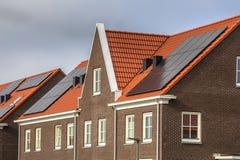 Σύγχρονα σπίτια σειρών με τα κόκκινα κεραμίδια και τα ηλιακά πλαίσια στεγών στοκ φωτογραφίες
