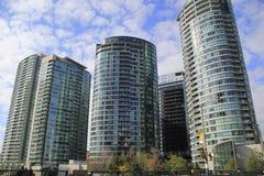Σύγχρονα, σύγχρονα γυαλιού πολυτέλειας κτήρια ανόδου Condo υψηλά ανασκόπησης ομάδων δεδομένων μπλε τσιμέντου σύννεφων κατασκευής  Στοκ Εικόνες