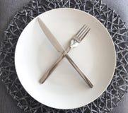 Σύγχρονες άσπρες πιάτο και ασημικές με το χαλί θέσεων στοκ φωτογραφίες