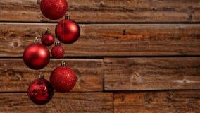 Σύγχρονες κόκκινες ακτινοβολώντας σφαίρες χριστουγεννιάτικων δέντρων που κρεμούν μπροστά από έναν ξύλινο τοίχο Στοκ εικόνες με δικαίωμα ελεύθερης χρήσης