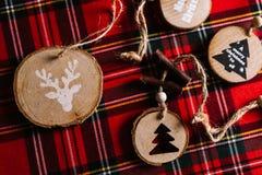 Σύγχρονες ξύλινες διακοσμήσεις με ένα μήνυμα Χριστουγέννων για τη διακόσμηση, σε ένα κόκκινο υπόβαθρο ταρτάν αφηρημένο ανασκόπηση στοκ εικόνες με δικαίωμα ελεύθερης χρήσης