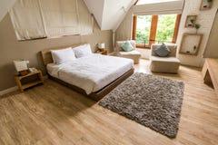Σύγχρονη άσπρη κρεβατοκάμαρα στο ξύλινο πάτωμα Στοκ φωτογραφία με δικαίωμα ελεύθερης χρήσης