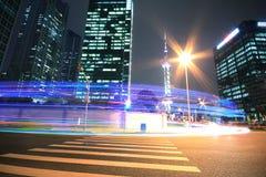 Σύγχρονη ανασκόπηση κτιρίου γραφείων της νύχτας αυτοκινήτων με τα ελαφριά ίχνη Στοκ Εικόνες