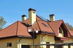 Σύγχρονη αττική στέγη σπιτιών με τα παράθυρα φεγγιτών, την υδρορροή στεγών, τις καπνοδόχους και τα ηλιακά πλαίσια Στοκ φωτογραφίες με δικαίωμα ελεύθερης χρήσης