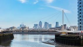 Σύγχρονη γέφυρα ποδιών πέρα από τον ποταμό με την οικονομική περιοχή του Λονδίνου ` s στοκ φωτογραφία με δικαίωμα ελεύθερης χρήσης