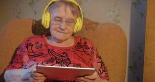 Σύγχρονη γιαγιά με το PC ταμπλετών και τα ακουστικά φιλμ μικρού μήκους