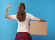 Σύγχρονη γυναίκα με το κουτί από χαρτόνι που παρουσιάζει δικέφαλους μυς στο μπλε Στοκ Εικόνες