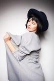 Σύγχρονη γυναίκα με το μαύρο καπέλο σε γκρίζο Στοκ Φωτογραφία