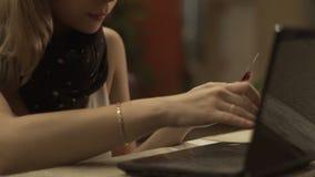 Σύγχρονη γυναίκα που χρησιμοποιεί την πλαστικά τραπεζική κάρτα και το lap-top για on-line να ψωνίσει σε Διαδίκτυο απόθεμα βίντεο