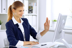 Σύγχρονη επιχειρησιακή γυναίκα στο γραφείο που παρουσιάζει εντάξει σημάδι στο όργανο ελέγχου υπολογιστών στοκ εικόνες