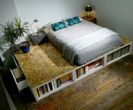 Σύγχρονη καθιερώνουσα τη μόδα κρεβατοκάμαρα με το κρεβάτι σε μια πλατφόρμα Στοκ εικόνα με δικαίωμα ελεύθερης χρήσης