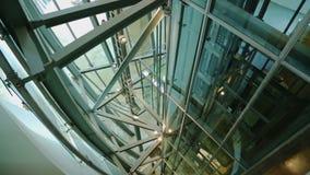 Σύγχρονη κατασκευή μετάλλων του άξονα ανελκυστήρων γυαλιού με τον ανελκυστήρα που ανεβαίνει και κάτω φιλμ μικρού μήκους