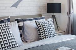 Σύγχρονη κρεβατοκάμαρα με τα γραπτά μαξιλάρια και το μαύρο λαμπτήρα Στοκ φωτογραφίες με δικαίωμα ελεύθερης χρήσης