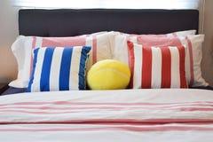 Σύγχρονη κρεβατοκάμαρα με τα μπλε, κίτρινα και κόκκινα ριγωτά μαξιλάρια Στοκ Εικόνα