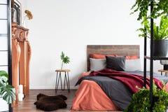 Σύγχρονη κρεβατοκάμαρα με τα σεντόνια κοραλλιών, τη χάλκινα εστία και τα μέρη των εγκαταστάσεων στοκ εικόνα με δικαίωμα ελεύθερης χρήσης